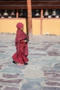 A novice monk walks across the courtyard of Hemis Gompa, Ladakh, India